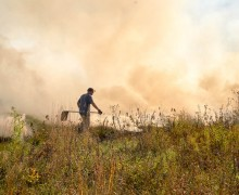 Charles Heide assists with a controlled burn in the prairie.