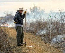 Steve Smith, a member of the work crew pauses to survey the burn for spreading flames.